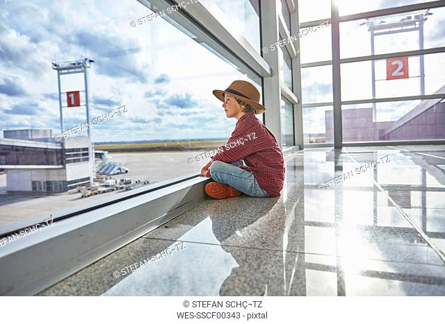 Boy sitting behind windowpane at the airport looking at airfield