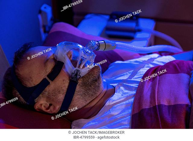 Man with sleep apnea syndrome, wears a CPAP mask while sleeping, breathing mask, which pushes air into the respiratory tract due to excess pressure and thus...