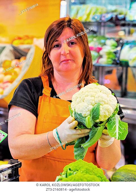 Unidentified saleswoman holding the cauliflower in Mercat de Santa Caterina - Fresh Food Market in Barcelona, Catalonia, Spain