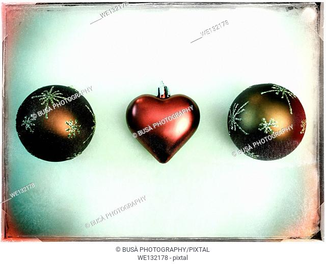Three christmas balls with the one in the center in the shape of a red heart