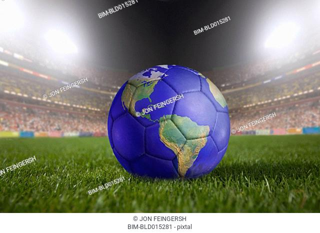 Soccer ball painted like a globe resting on grass in large stadium