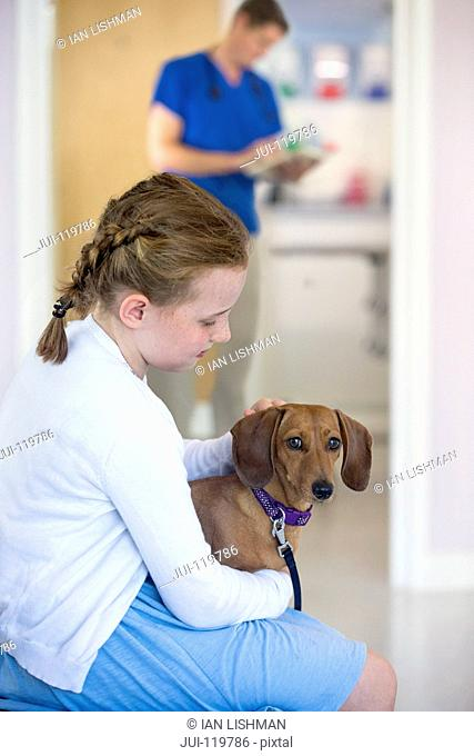 Child owner with pet dog in waiting room of vet surgery