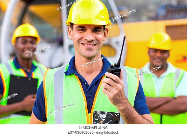 portrait of smiling contractor with walkie-talkie