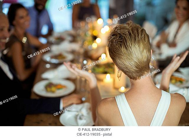 Woman clapping at dinner party