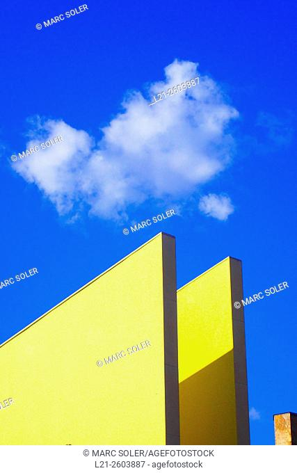 Architectural detail of triangular shape topped by a cloud on a blue sky. Barcelona, Catalonia, Spain