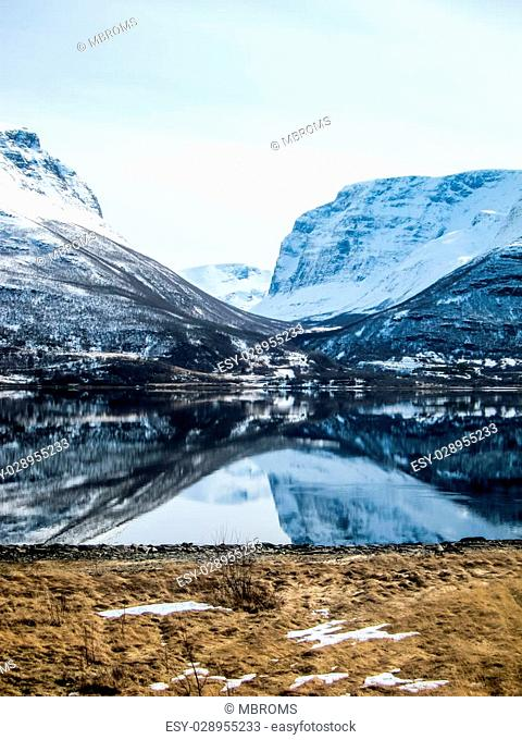 View of winter mountains mirrored in a perfectly calm fjord in the Lyngen Alps, Norway