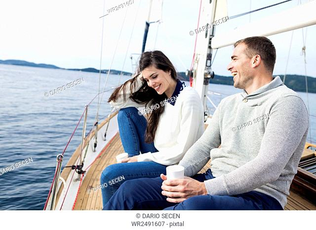 Young couple on yacht laughing