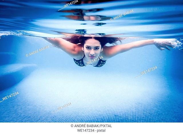 Young woman diving in swimming pool