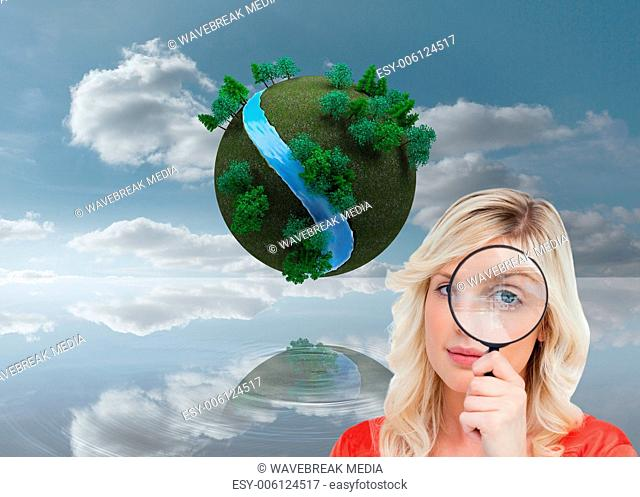 Composite image of fairhaired woman looking through a magnifying glass