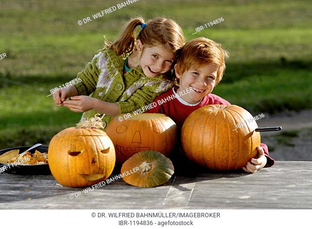 Two children carving pumpkins for Halloween decoration