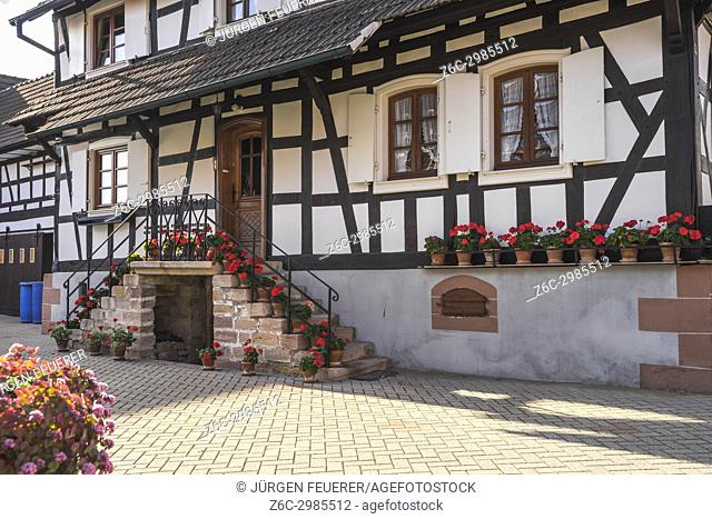 half-timbered houses with flower decoration in Hunspach, small village in Northern Alsace, North Vosges, France, member of the most beautiful villages of France