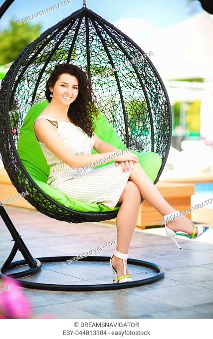 pretty brunette woman relaxing on a lounger outdoors