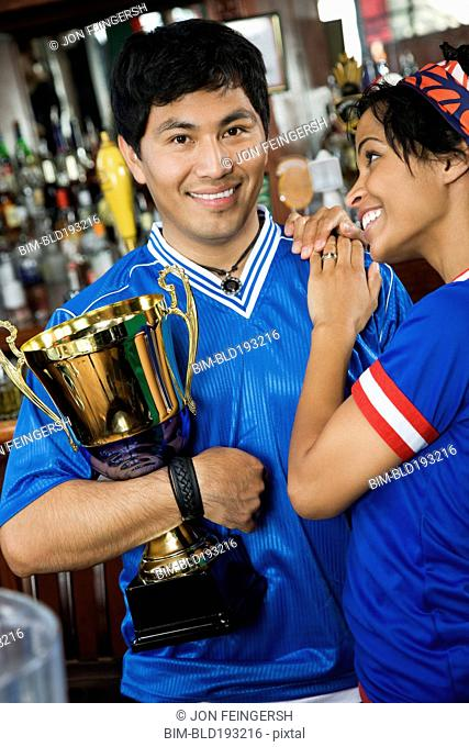 Woman hugging boyfriend with trophy