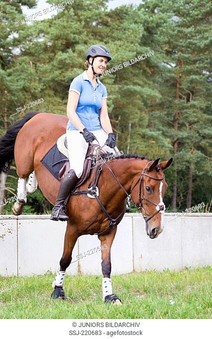 Irish Sport Horse. Rider clearing an in-out-obstacle during a cross-country ride. Germany
