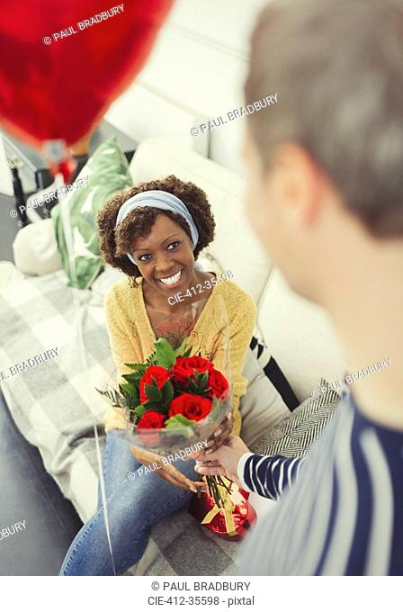 Husband giving Valentine's Day rose bouquet and balloon to wife
