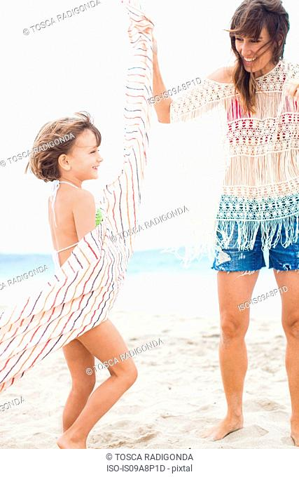 Mother twirling striped towel around daughter