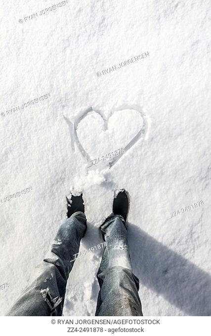 Vertical details on the legs of a male traveler standing in 1st person point of view with heart drawn in the snow. Cold feet or winter holiday love