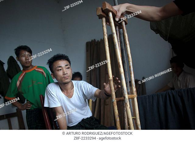 Kachin's militia member Lalaw Ze Dai, from Waimaw village, 25, catch his crutches in the General Military Hospital in Laiza village close to the China border