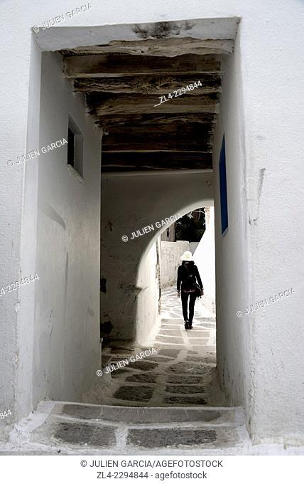 Woman walking in a narrow street in the old town of Parikia. Greece, Greek islands in the Aegean sea, the Cyclades, Paros island. Model Released