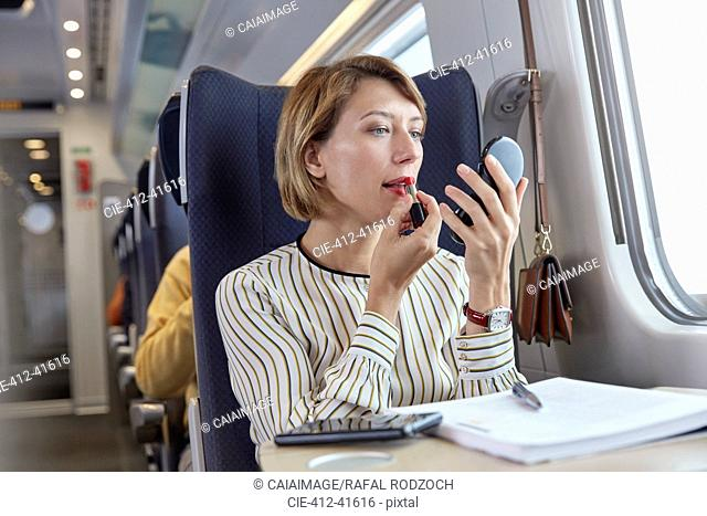 Businesswoman applying lipstick with makeup contact on passenger train