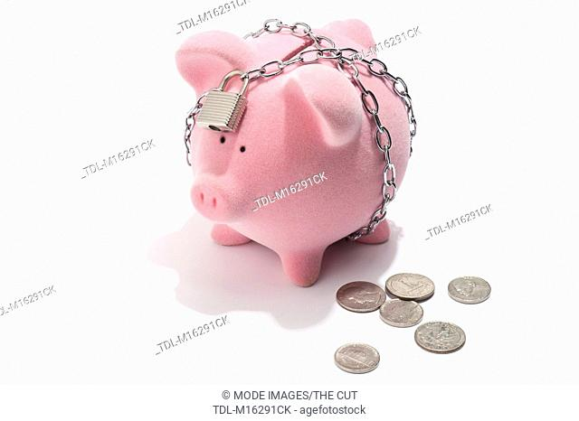 A chained and padlocked piggy bank with US coins next to it