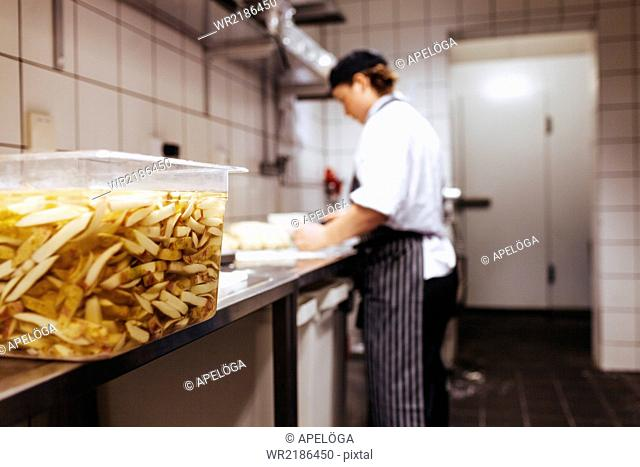 Close-up of potato chips soaked in water with chef working in background