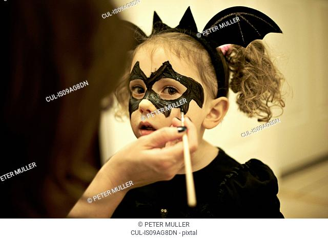 Mother painting daughters face for halloween bat costume