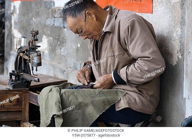 Shoe repairer at work in Tangmo heritage village, Huizhou, Anhui, China