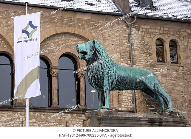 "24 January 2019, Lower Saxony, Goslar: A flag with the inscription """"Deutscher Verkehrsgerichtstag"""" (German Traffic Court Day) is flying next to a bronze..."