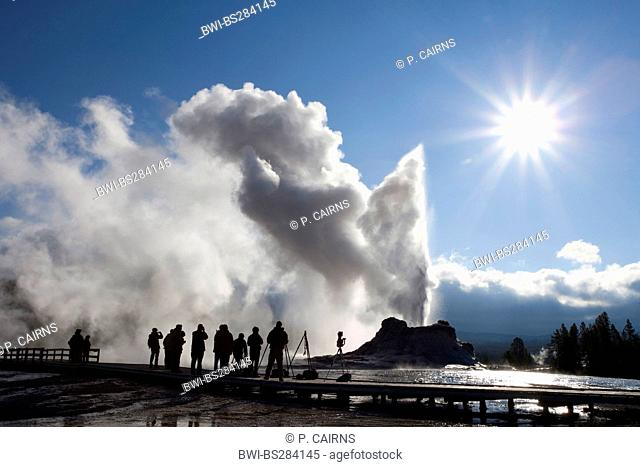 photographer at erution of Castle Geyser at Old Faithful geothermal area, USA, Wyoming, Yellowstone National Park