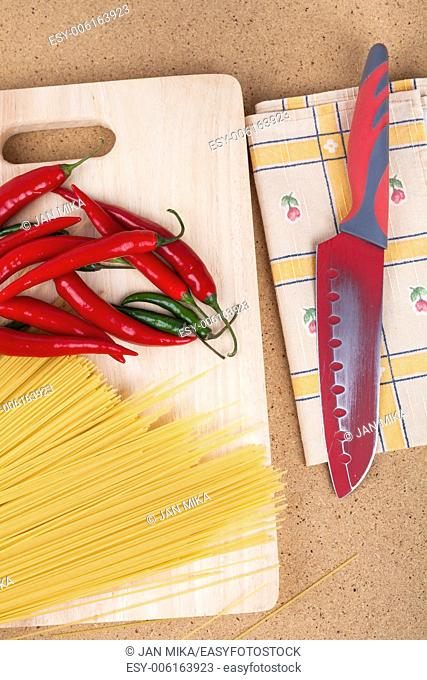 Dried uncooked pasta and chili peppers on chopping board