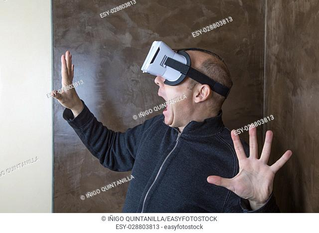 adult man with virtual reality headset, or 360 glasses, grey cardigan with zipper, terrified face expression and gesture, indoor home