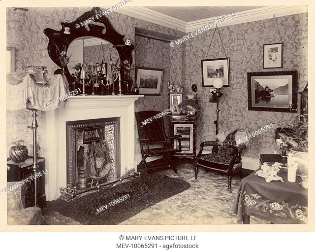 The corner of a middle-class sitting room, with ornaments in the characteristic cast- iron fireplace with its tile surround, and on the mantel