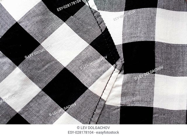 clothes and textile concept - close up of checkered clothing item with pocket