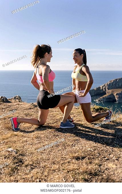 Spain, Asturias, two sportswomen training on the coast, knee bend