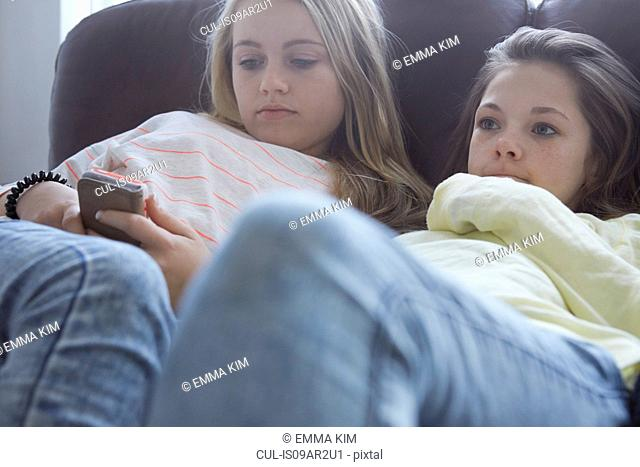 Two girls watching tv and smartphone texting on sofa