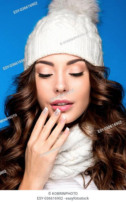 Beautiful girl with a gentle make-up, design manicure and a smile in winter white knit cap. Warm winter image. Beauty face
