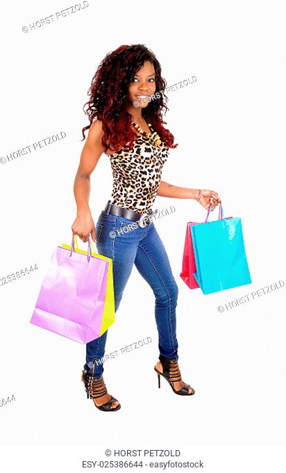 A lovely sling young African American woman holding her colorful shopping .bags, smiling, standing isolated for white background.