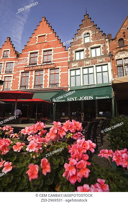 Traditional buildings on the Market Square with flowers in the foreground, Bruges, West Flanders, Belgium, Europe