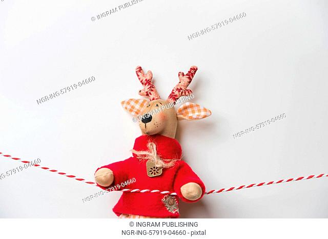 Handmade vintage Christmas deer hanging on a ribbon on white background with copyspace