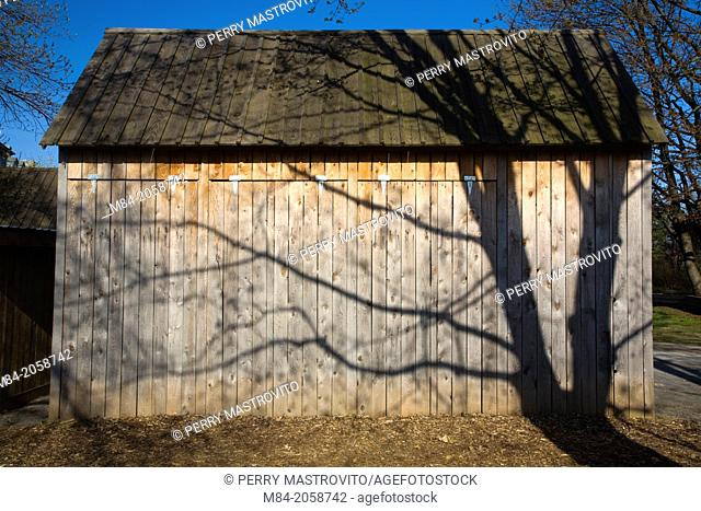 Tree shadows on rustic wooden storage shed, Ile des Moulins, Old Terrebonne, Lanaudiere, Quebec, Canada