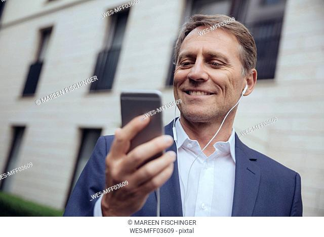 Portrait of smiling mature businessman outdoors with earphones and smartphone