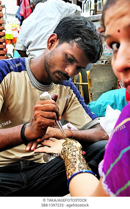 Henna hand painting on the street in Paharganj, India