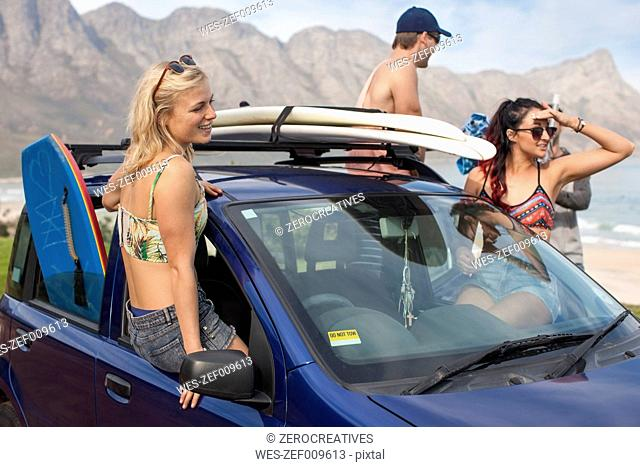Friends with surfboards on car at the coast