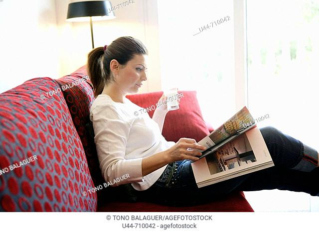 Woman drinking a milk glass reading a book relaxed on the sofa