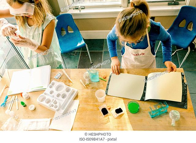 Overhead view of two girls doing science experiment, reading chemistry set instructions