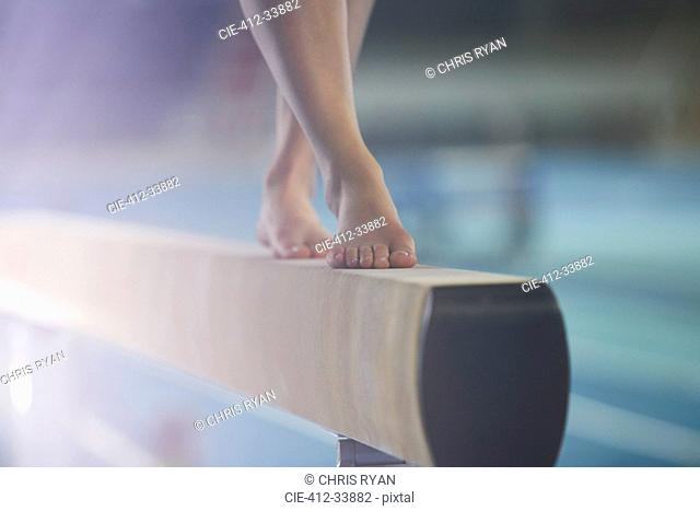 Bare feet of female gymnast performing on balance beam