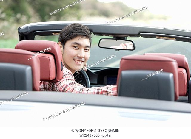 Side view portrait of young smiling man in a car looking back