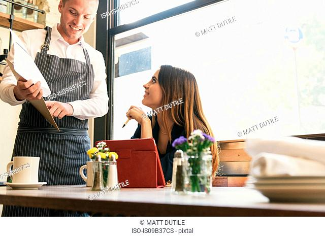 Young woman and waiter discussing menu in restaurant