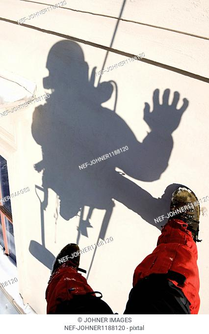 Shadow of construction worker hanging on rope